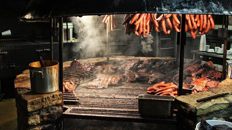 Sausages and brisket being smoked over a large barbecue pit