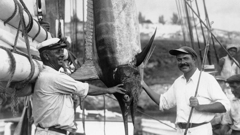 Ernest Hemingway, right, with a fishing rod and a marlin, while Captain Joe Russell from Key West looks on