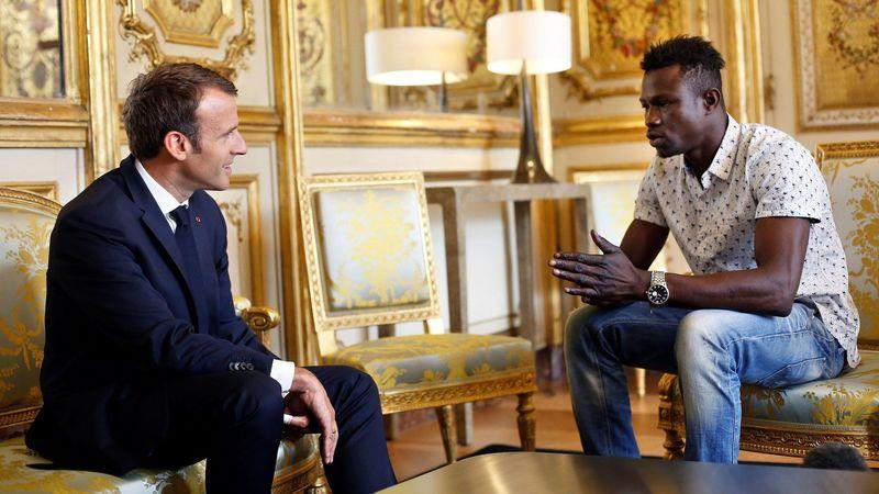 President Emmanuel Macron (left) speaks to Mamoudou Gassama